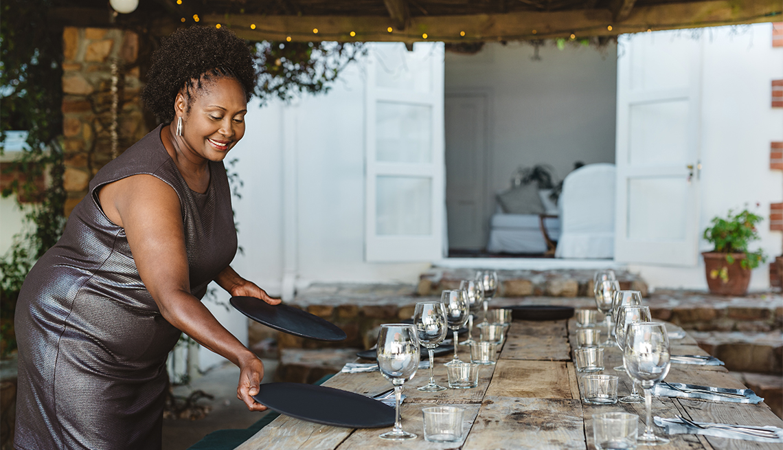 Smiling woman wearing an evening gown setting up a table for a dinner party on her outdoor patio