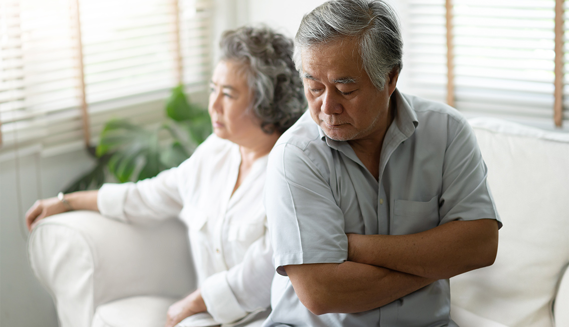 Upset man sitting on the edge of the sofa with arms crossed against the background of his wife.