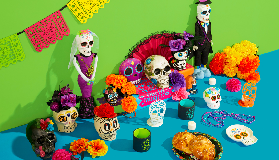 a tabletop decorated for dia de los muertos with skeletons and food offerings