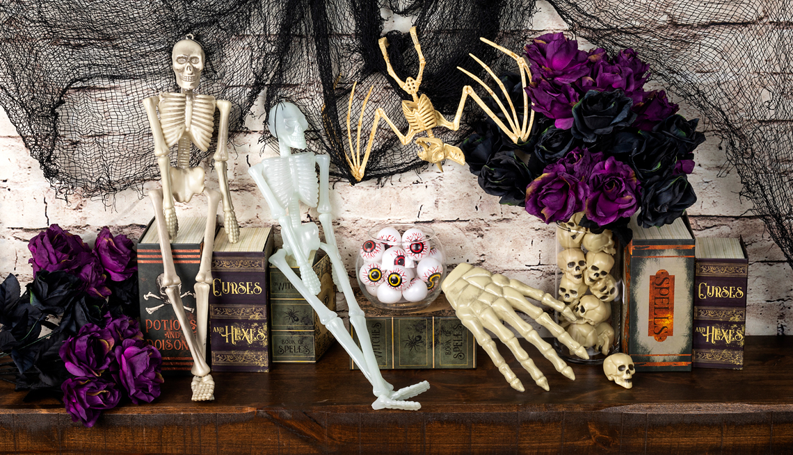 a mantle decorated for halloween with skeletons and eyes and flowers