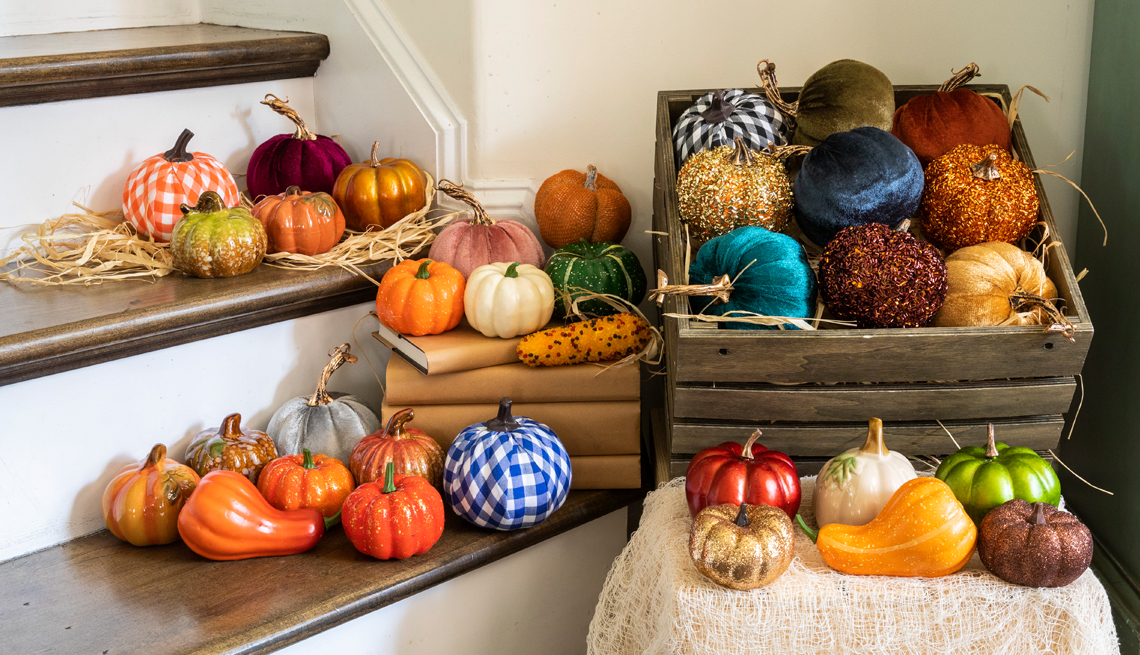 an assortment of colorful pumpkins in a basket and on the stairs