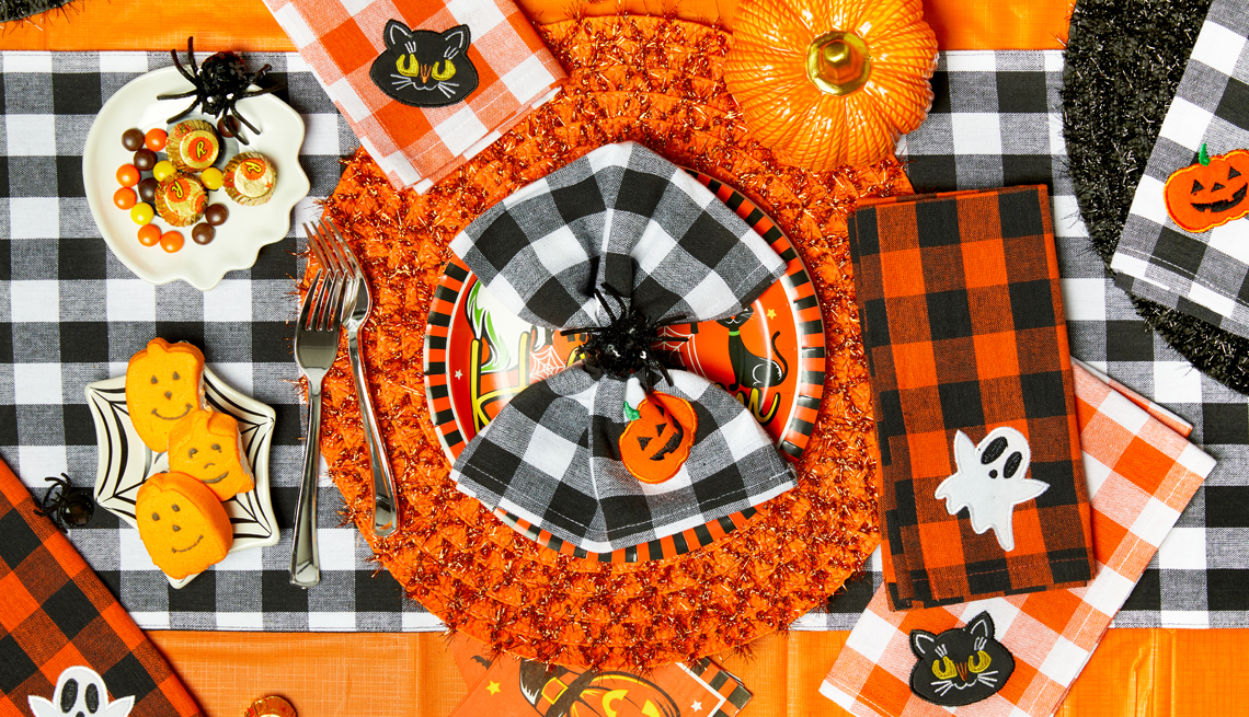a tabletop decorated for halloween with pumpkins and candy and spiders and cats