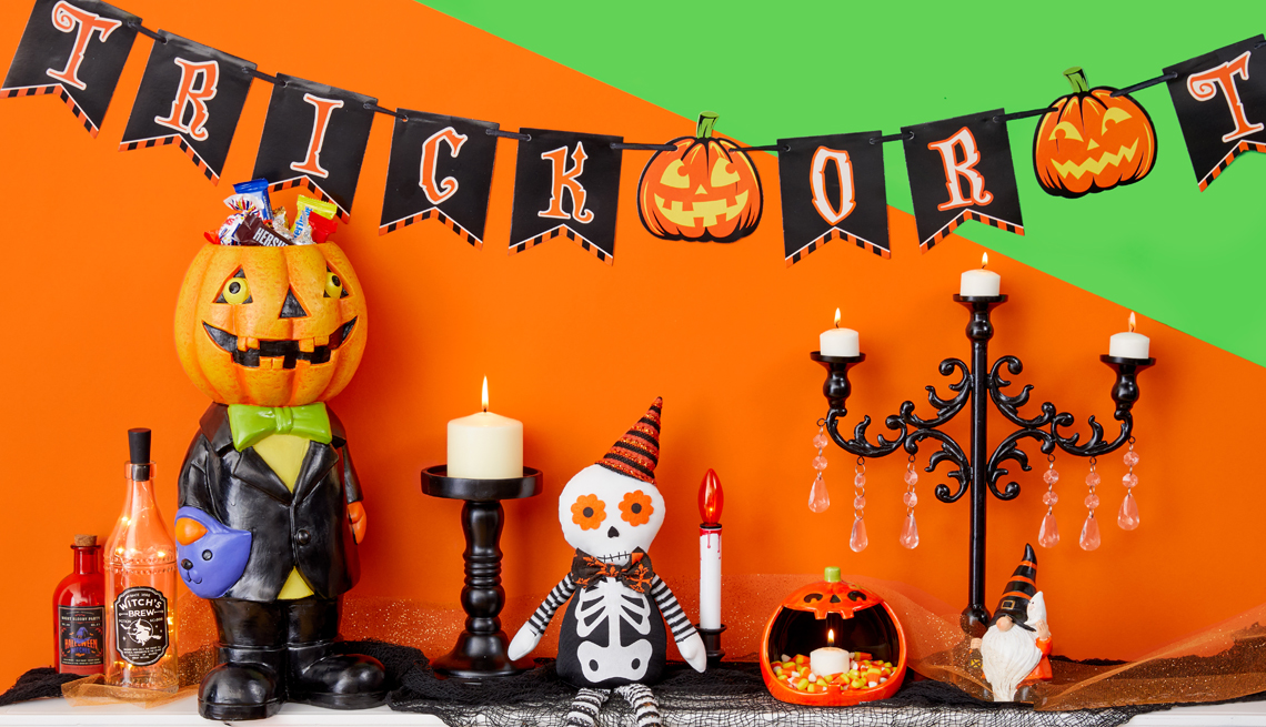 a mantle decorated for halloween with a trick or treat banner and candles and skeletons
