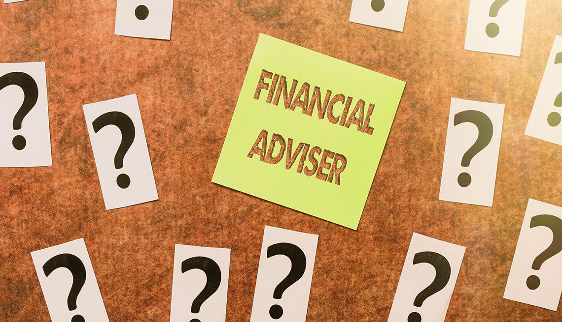 Tablero de notas con interrogantes y un papel de notas que dice asesor financiero en inglés