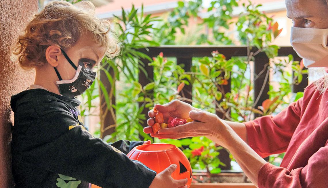 Un adulto pone caramelos en la canasta de un niño en Halloween