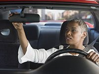 African American woman rear view mirror, safe car features
