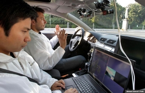 Driverless car self driving laser guided car computer two researchers hands free off wheel