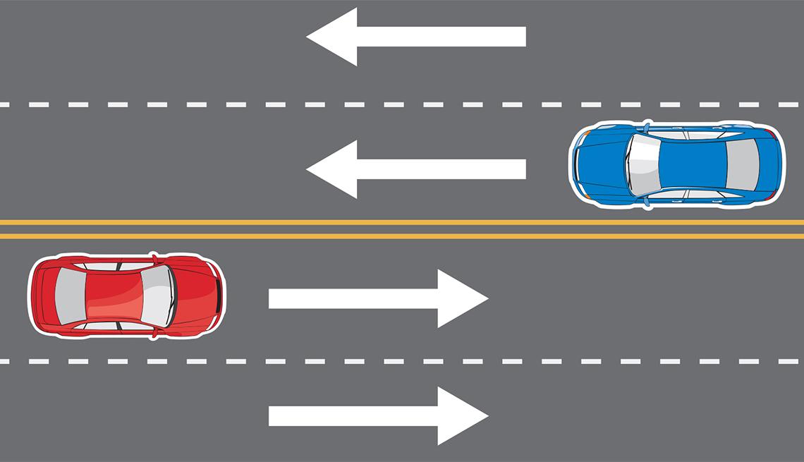 Dos autos transitan por una vía de 4 carriles, 2 en cada sentido