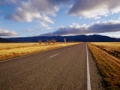 Rural highway in a field with mountains and clouds. (Rob Brown/Corbis)