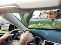 Man driving, reflection in rearview mirror . Driving Resource Center (Odilon Dimier/PhotoAlto/Corbis)