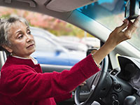 A woman adjusting car mirror, AARP Driver Safety Sweepstakes