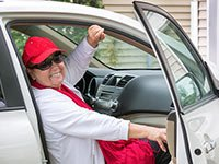 A woman gets a ride as she gets into the passenger side of a car