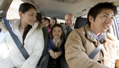 Multi-generation family in the car, smiling
