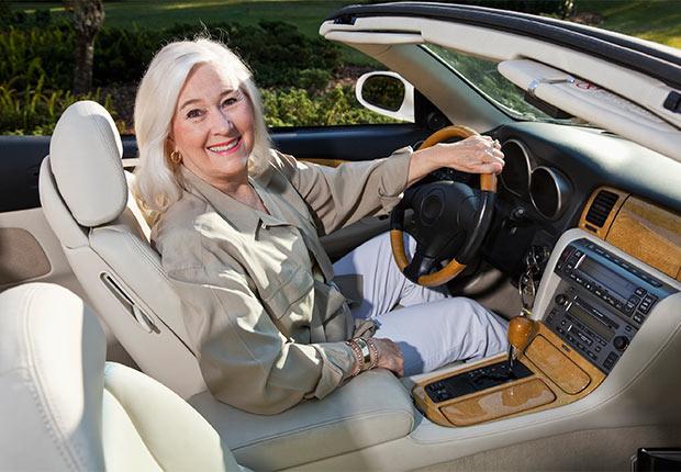 Mujer mayor sentada en su auto