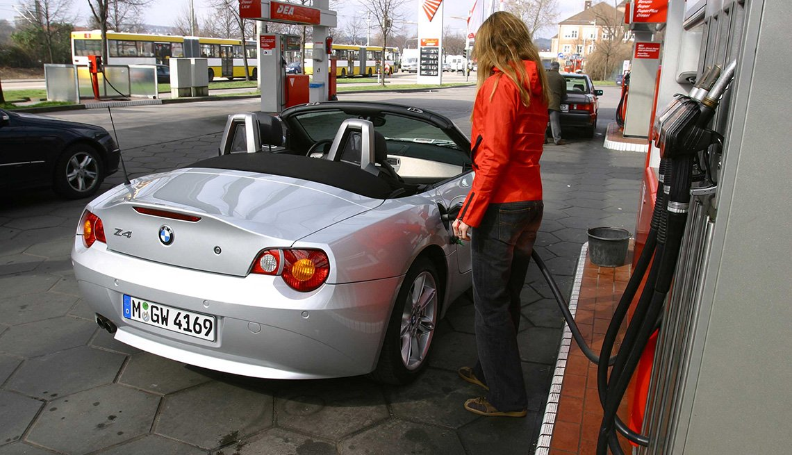 Woman pumping gas at a gas station, 6 things you need to know about buying and owning a convertible