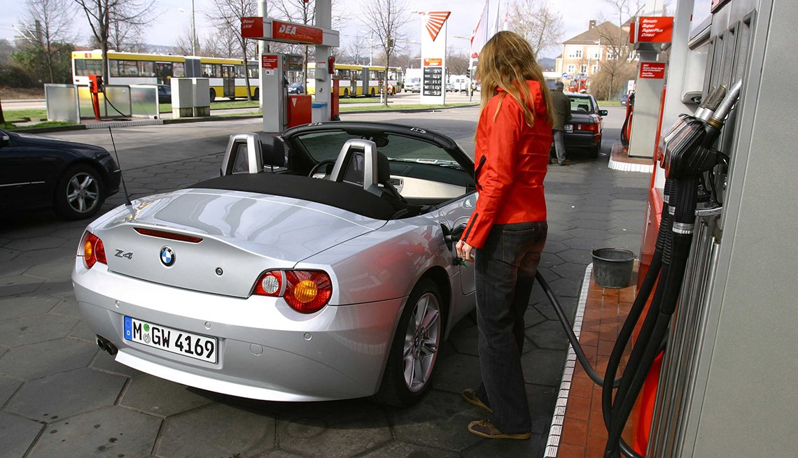 Woman Fuels A Convertible Higher Operating Costs Pros And Cons Of Ing