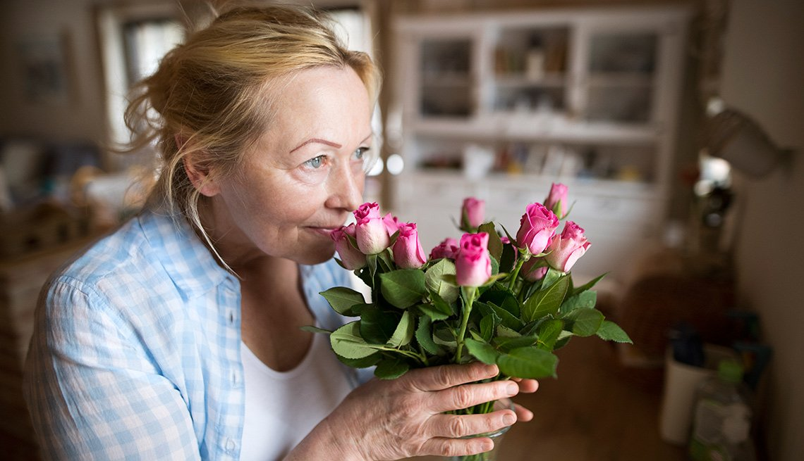 Mujer huele unas flores