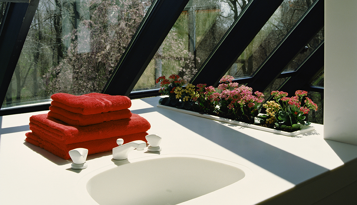 Un baño lleno de luz con dos toallas rojas sobre el lavamanos