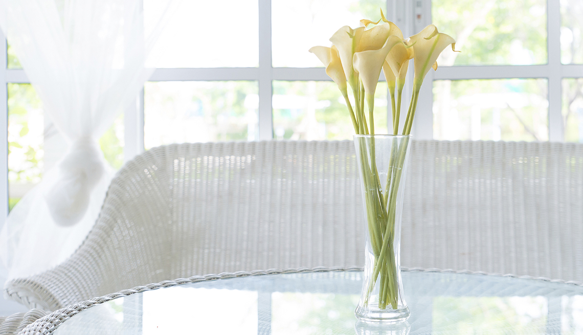 Flores amarillas en un vaso en una mesa de vidrio con una silla decorativa detrás