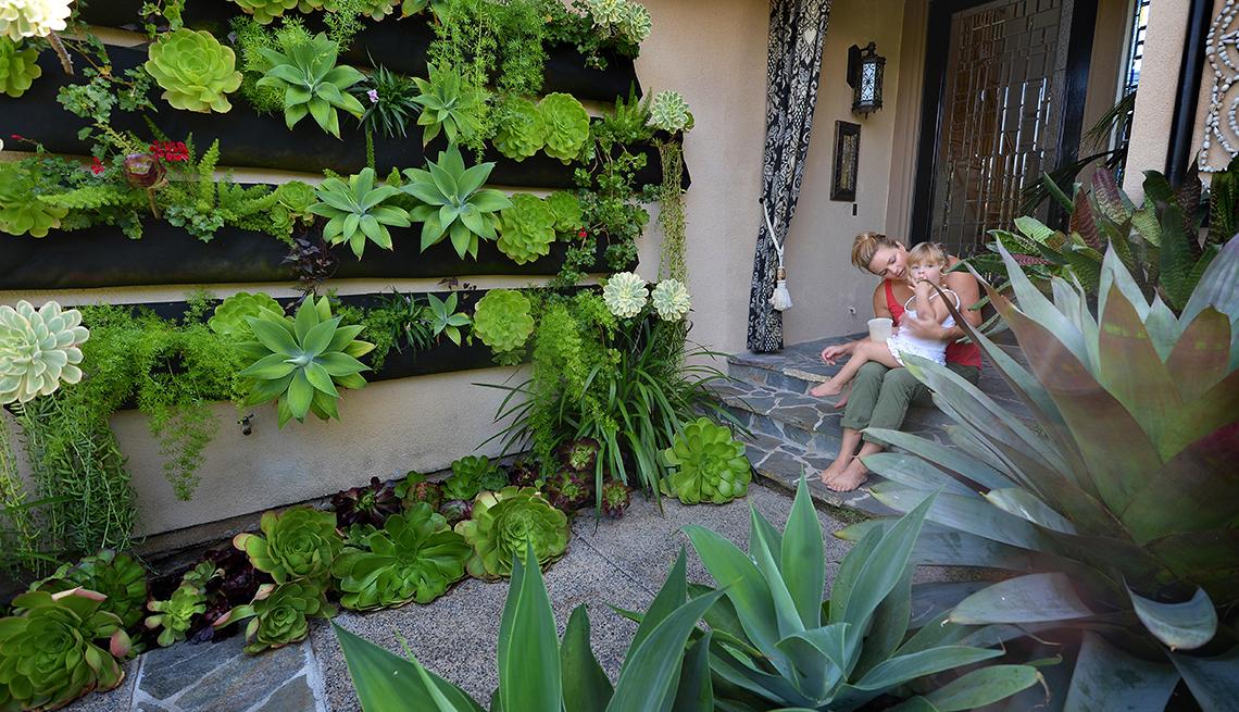 Mujer con una niña pequeña afuera de su casa en frente de un jardín vertical