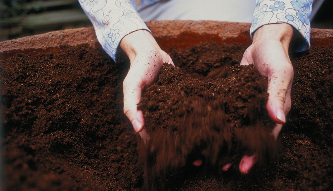 Manos de una mujer mezclando compostaje