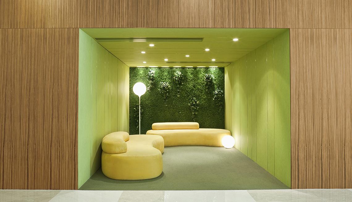 Interior con sofá moderno y una pared con jardín vertical