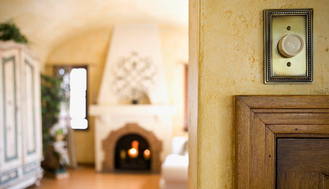 Un regulador de luz en la pared con una sala de estar en el fondo