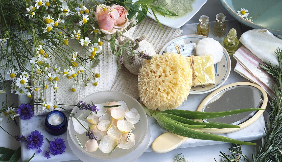 Mesa con flores y plantas, aloe vera, aceites aromáticos, esponja natural y jabones