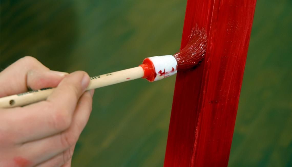 Acercamiento de mujer pintando mueble con pintura roja