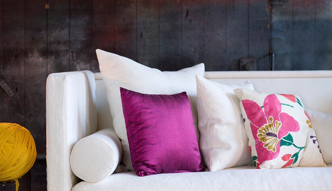 Sofá blanco decorado con cojines de colores