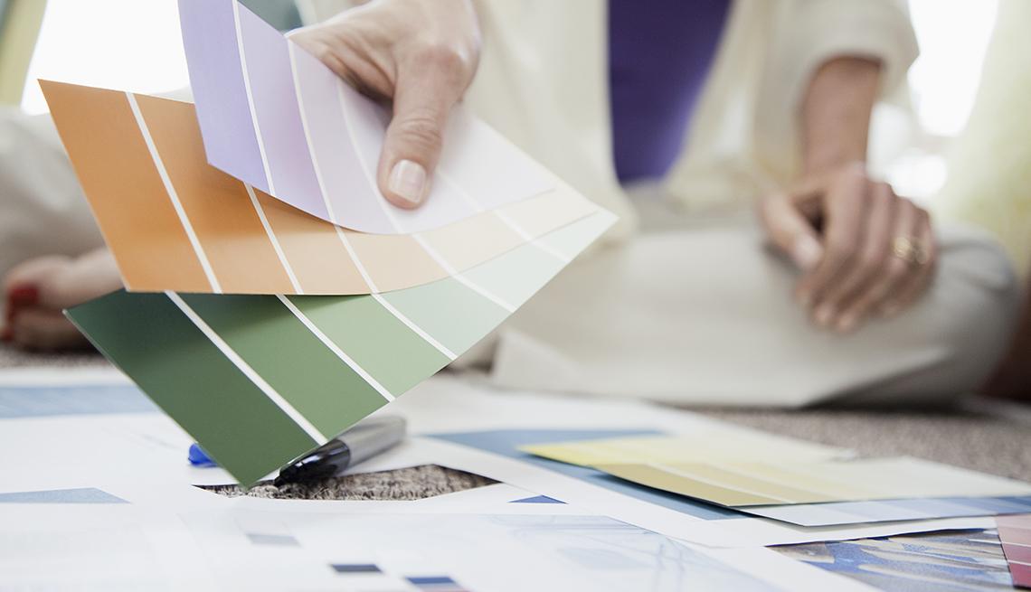 Mujer sostiene paletas de colores para pintura