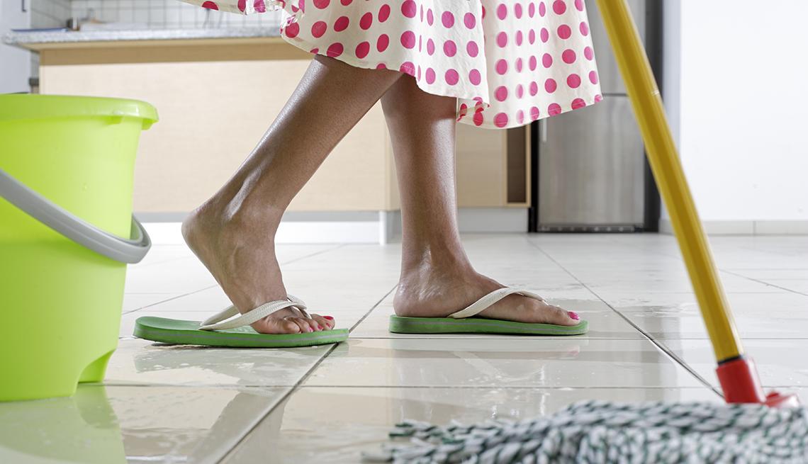 Mujer limpiando el piso de una cocina con trapero