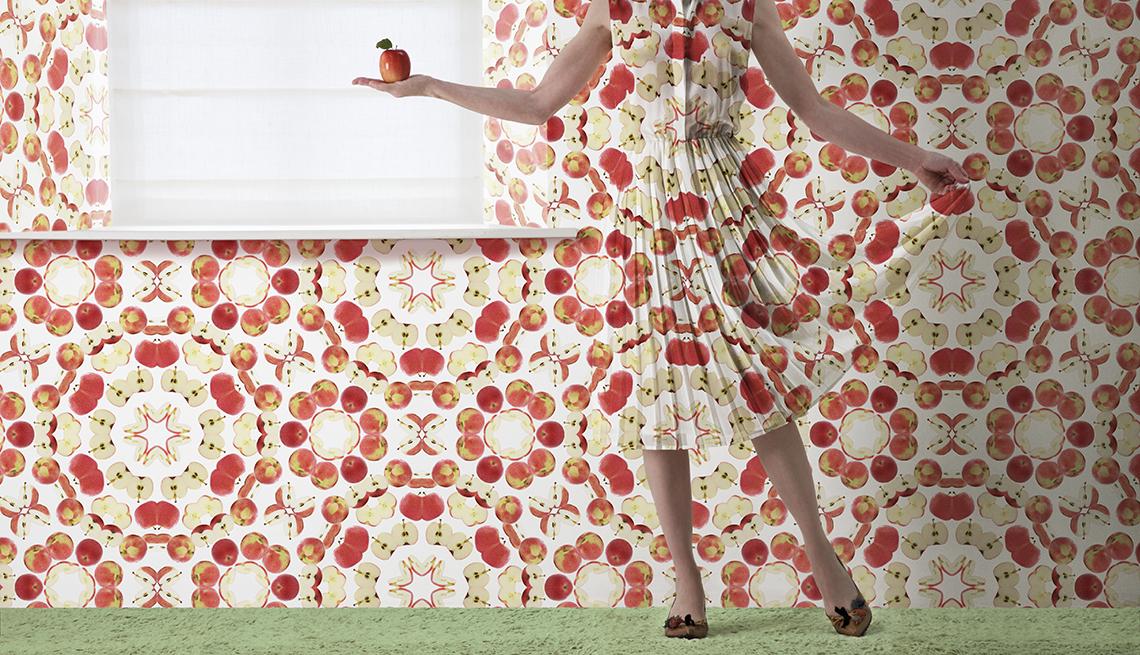 Mujer con vestido de colores brillantes y una pared empapelada con los mismo colores