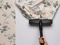 10 Errores a la hora de decorar - Mujer quitando un papel de colgadura con una aspiradora