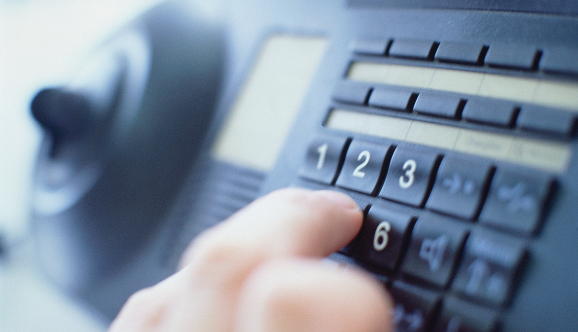 Close Up Of A Hand Dialing A Number On A Landline Phone, AARP Home And Family, 10 Tips To Prevent Accidents At Home