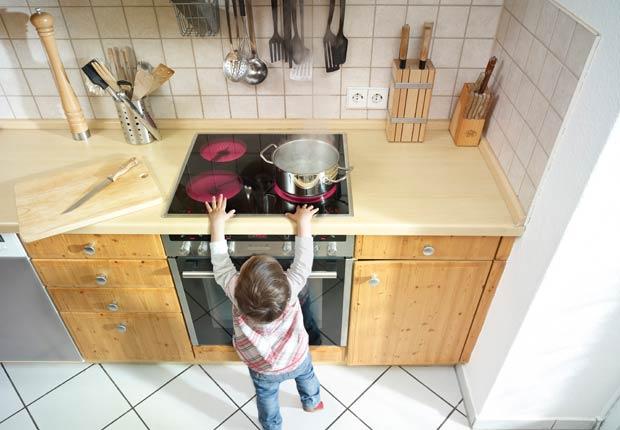 El pequeño niño se coloca cerca de una estufa, 10 consejos para prevenir accidentes en el hogar