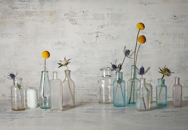 Flores frescas cortadas en pequeñas botellas de la vendimia, Mezcla lo antiguo con lo nuevo