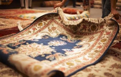 Persona mirando una alfombra de una tienda - 3 Consejos para elegir, cuidar y decorar con alfombras