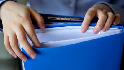 Mujer buscando documentos en una carpeta - Organizar sus documentos para la temporada de impuestos y para todo el año