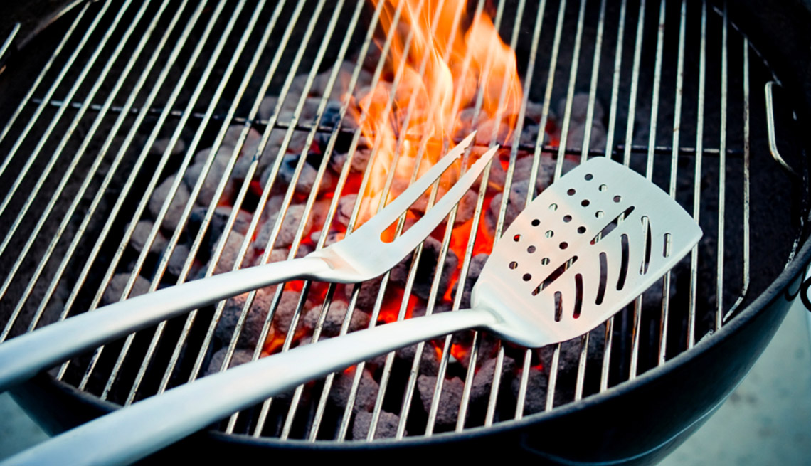 Barbeque Tongs Sit On Grill With Flame In Background, AARP Home And Family, Home Improvement, How To Get The Best Grille