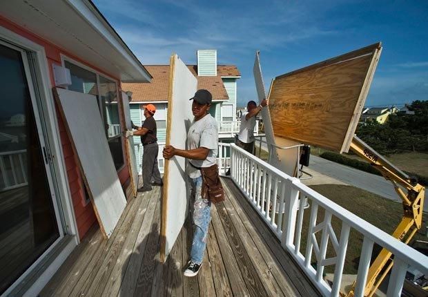 Hombres poniendo plancas de plywood en una casa junto a la playa, mientras se preparan para un huracán, los pasos para preparar su hogar para los huracanes