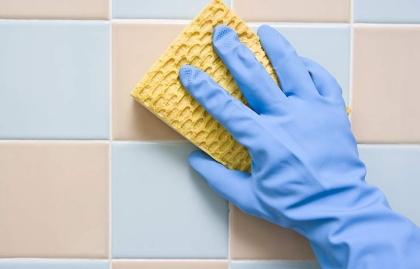Claves para que tu baño luzca siempre limpio - Mano fregando la pared de la ducha