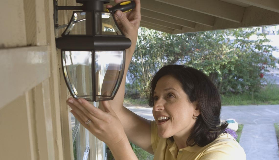 Woman cleaning light fixture, 10 Ways to Add a Curb Appeal to your Home
