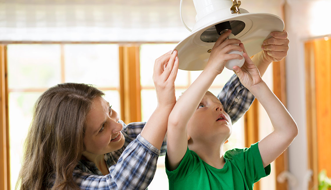 Niño cambia una bombilla ayudado por una mujer