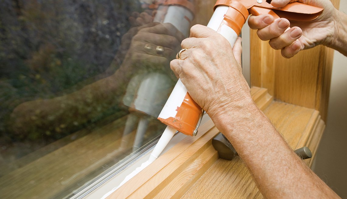 Persona sellando una ventana