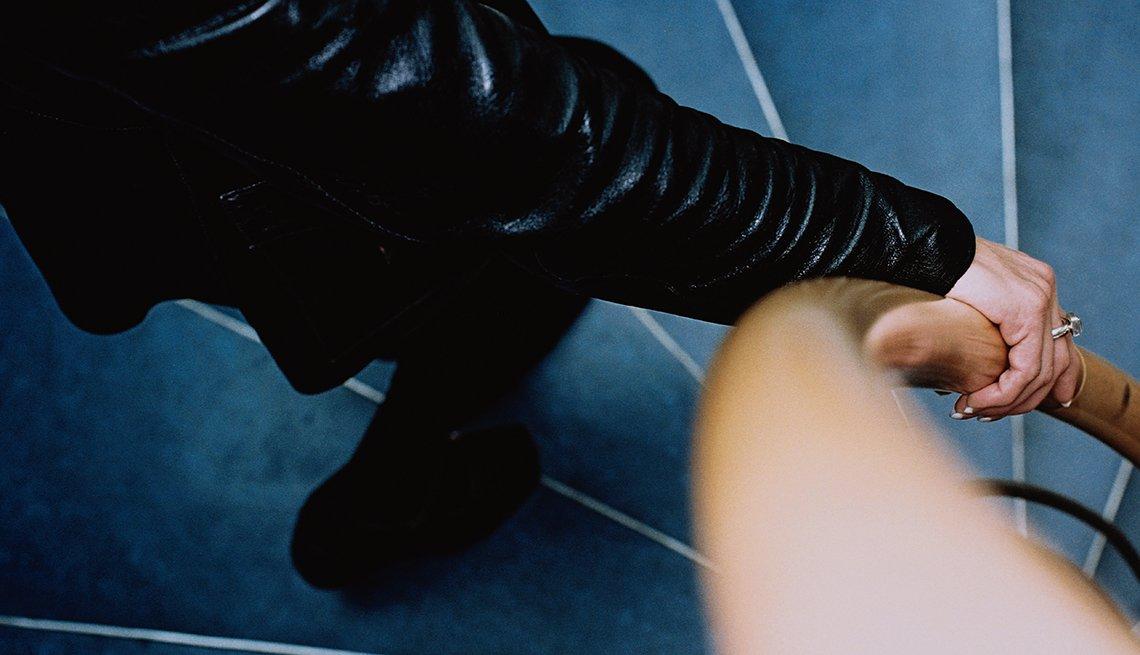 Mujer usando el pasamanos en la escalera, 10 consejos para prevenir accidentes en el hogar
