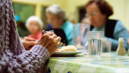 Several elderly people dining at a table.