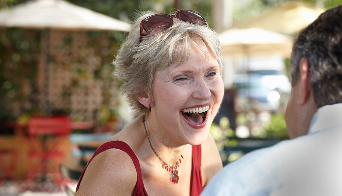 AARP recommends ten cities where older singles can retire well- a woman laughing while sitting in a cafe