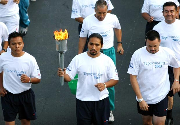 Fernando Juárez, quien lleva la Antorcha Guadalupana desde la Basílica de Guadalupe en Ciudad de México, corre en companía de otros corredore