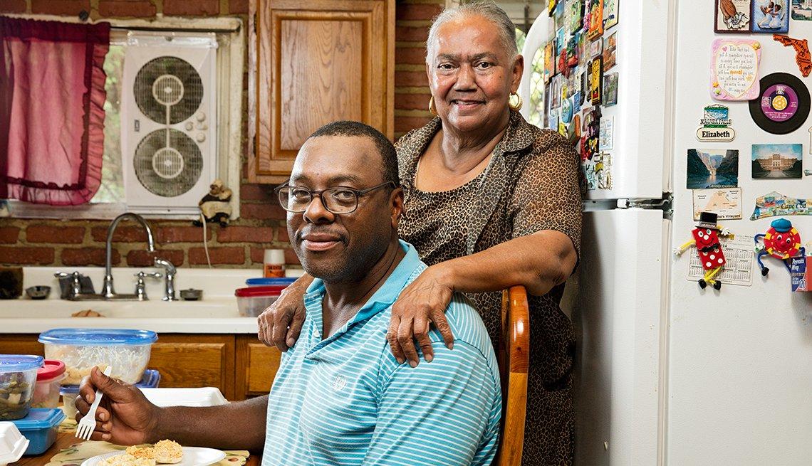 Alethea Booze, right, makes dinner for neighbor Patrick Scott in Baltimore's Sandtown neighborhood.